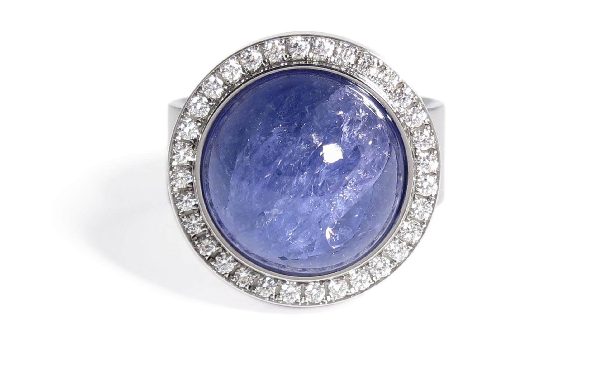 Stainless steel ring featuring a blue tanzanite gem stone with white diamonds set around it by custom jewelry designer Stefan Witjes