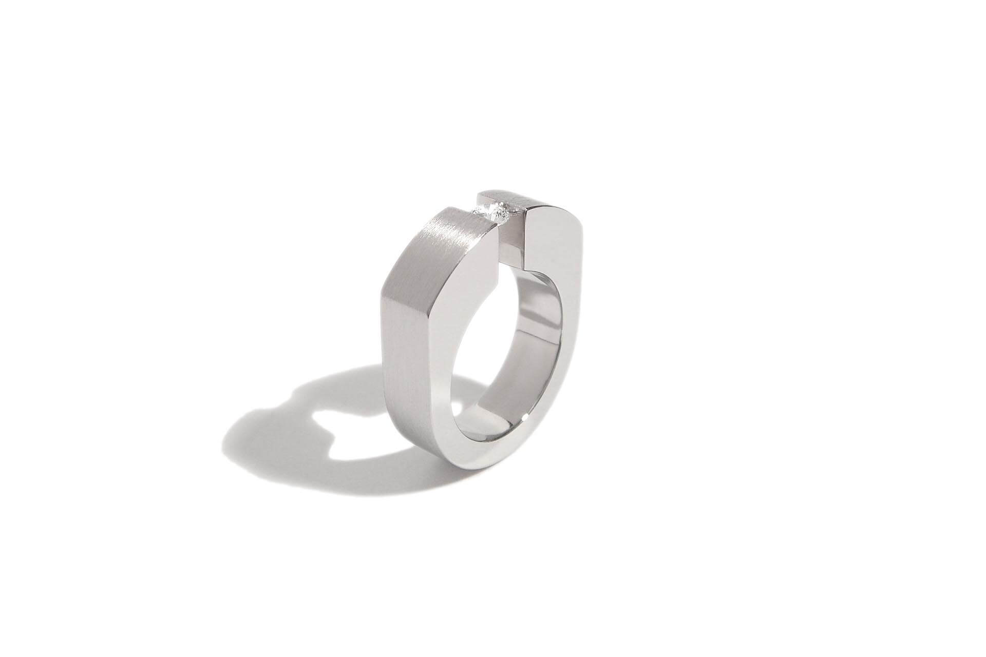 Stainless steel ring with tension set diamond