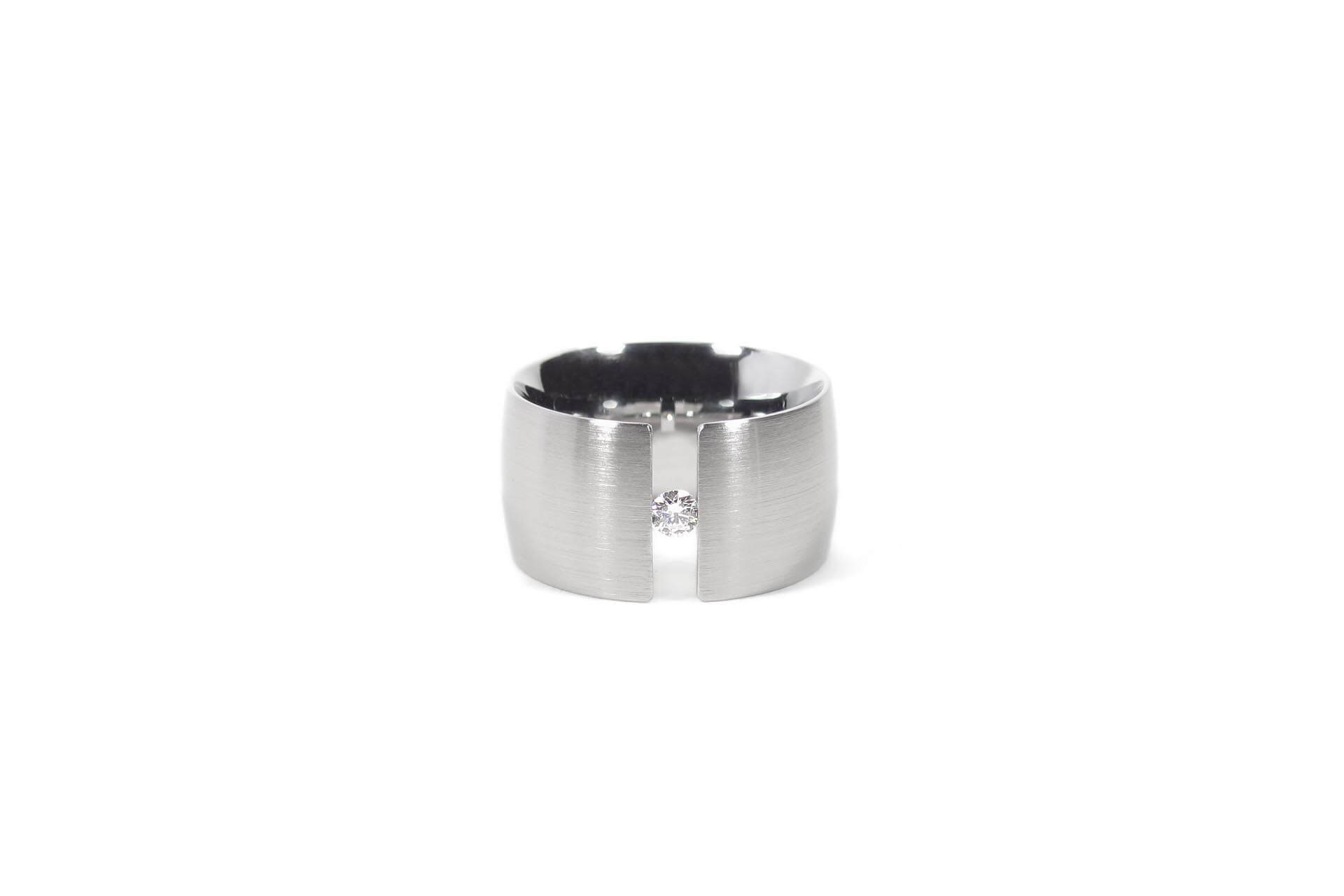 Oval stainless steel ring with a tension set diamond