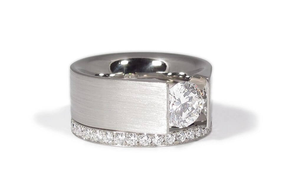 Close up of Stacy's engagement and wedding ring. Platinum ring featuring a white solitaire brilliant diamond and matching band with eternity diamonds.