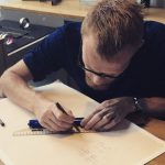Stefan Witjes, master goldsmith drawing out design of custom jewelry.