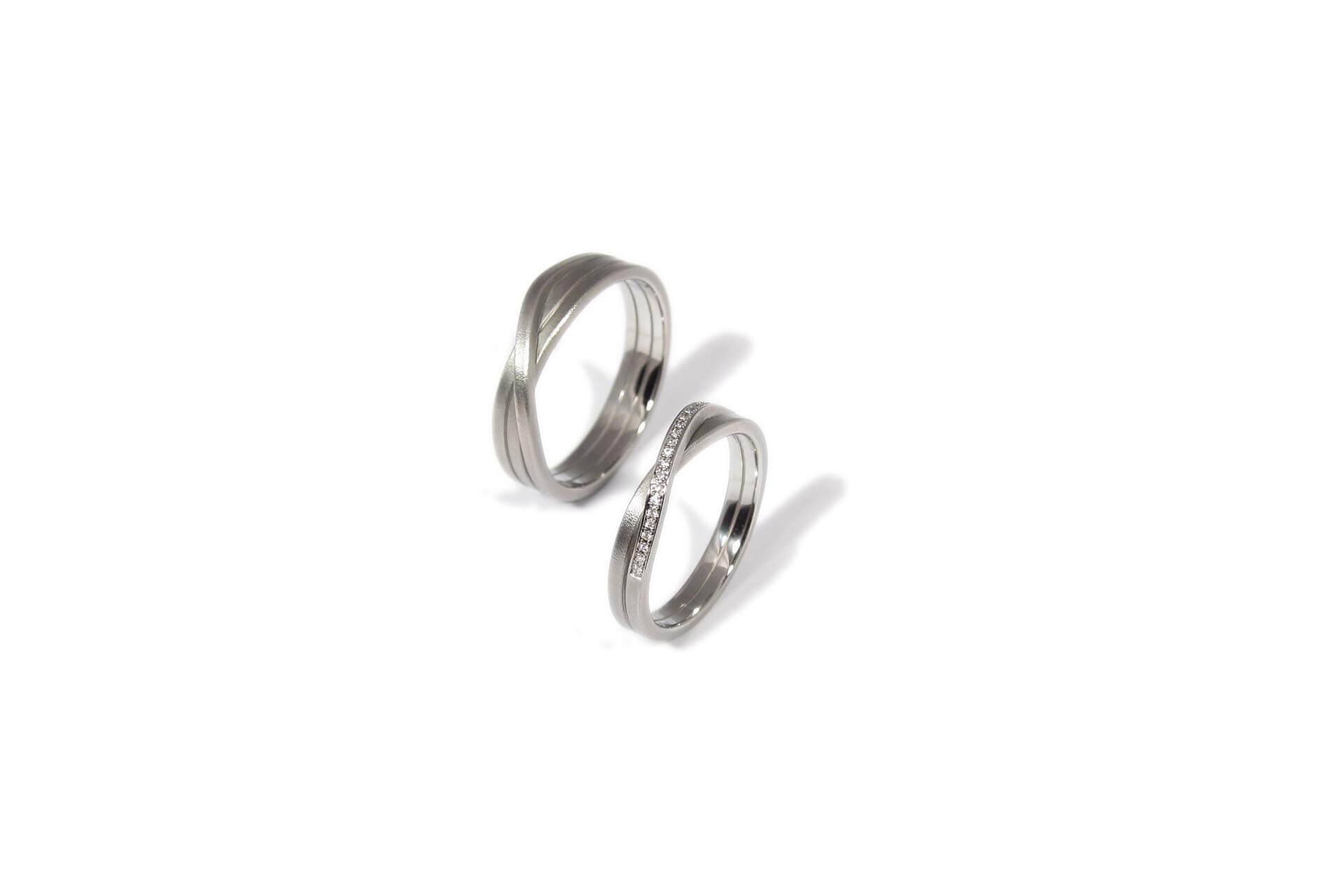 Oliver Schmidt stainless steel knot rings with the woman's band featuring a row of white diamonds.
