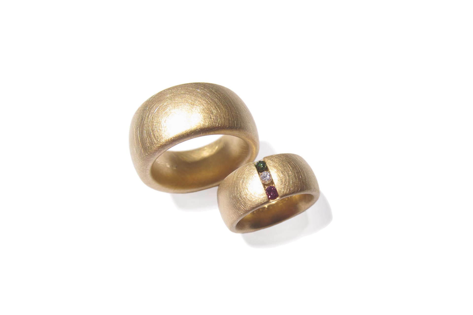 Two yellow gold oval rings with a scratched matte finish. One right has a diamond, a pink tourmaline, and a green tourmaline.